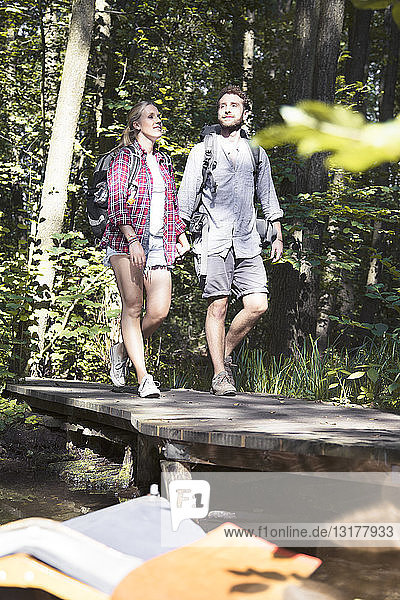 Young couple crossing a bridge in forest