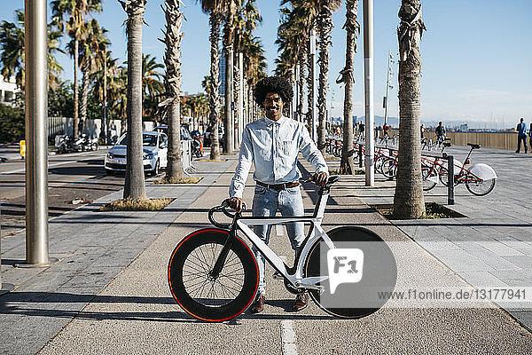 Mittelgroßer erwachsener Mann steht auf der Straße und zeigt sein Fixie-Bike