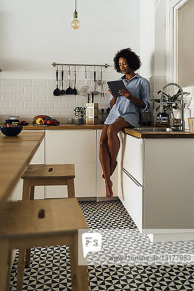 Woman sitting on worktop of her kitchen  using digital tablet in the morning