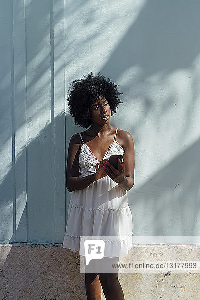 Young woman wearing white dress using cell phone at a wall