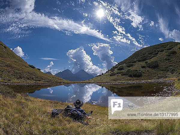 Italien  Lombardei  Bergamaskische Alpen  Wandern am Seeufer liegend  Blick auf den Berg Camino