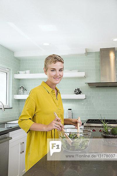 Porträt einer lächelnden jungen Frau  die in der Küche Salat zubereitet