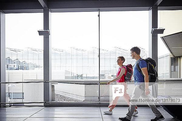 Lächelndes Paar beim Spaziergang am Flughafen