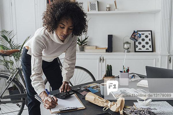 Freiberufler am hert-Schreibtisch stehend  mit Taschenrechner  Notizen machen