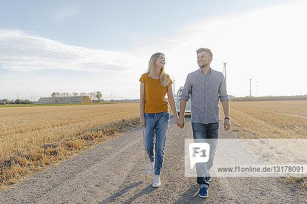 Junges Paar geht auf Feldweg mit Wohnmobil in ländlicher Landschaft