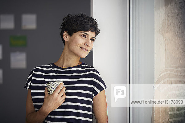Smiling woman with cup of coffee looking out of window