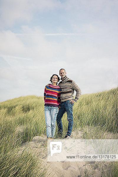 In den Dünen stehendes reifes Paar  die Arme um den Körper gelegt
