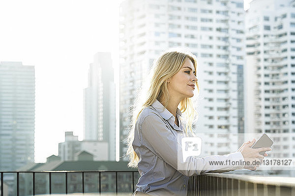 Portrait of blonde business woman leaning onto handrail on city rooftop