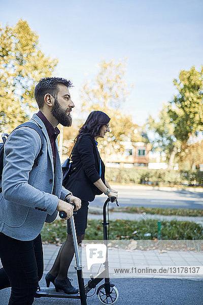 Geschäftsmann und Geschäftsfrau auf dem Roller