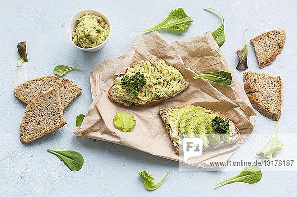 Brotscheiben mit geschnittener Avocado und Avocadocreme auf braunem Papier