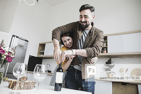 Portrait of happy couple with bottle of red wine in the kitchen