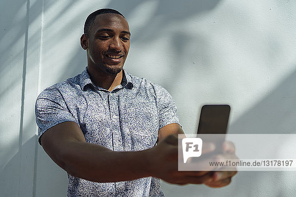 Smiling young man wearing shirt taking a selfie at a wall