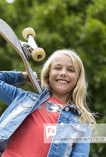Portrait of proud blond girl with skateboard on her shoulder