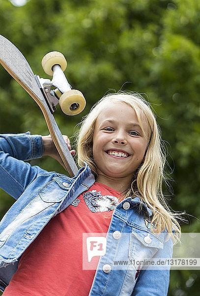 Portrait of proud blond girl with skateboard on her shoulder