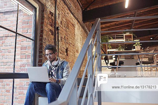 Geschäftsmann sitzt auf der Treppe eines modernen Büros und benutzt einen Laptop