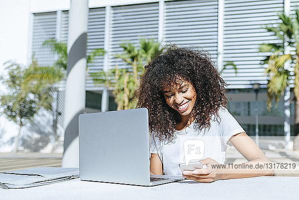 Lächelnde junge Frau mit Laptop  die mit einem Smartphone an einem Tisch im Freien sitzt
