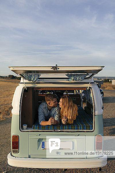 Junges Paar liegt im Wohnmobil in ländlicher Landschaft