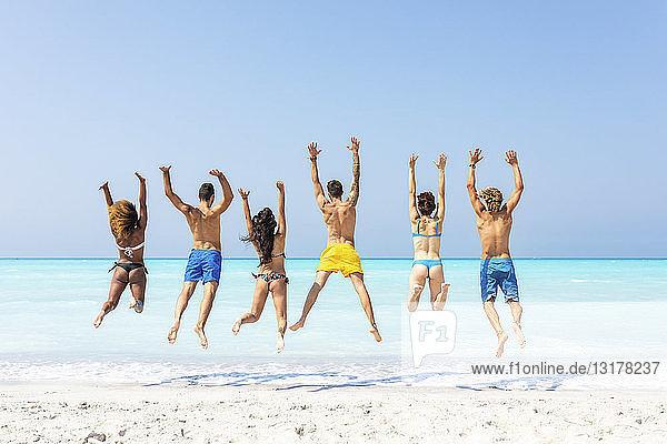 Gruppe von Freunden am Strand  die vor Freude hüpfen