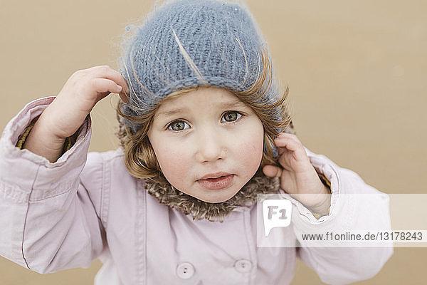 Porträt eines unglücklichen kleinen Mädchens am Strand im Winter