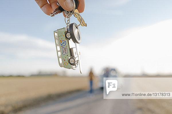 Wohnmobilschlüssel in der Hand haltend in ländlicher Landschaft