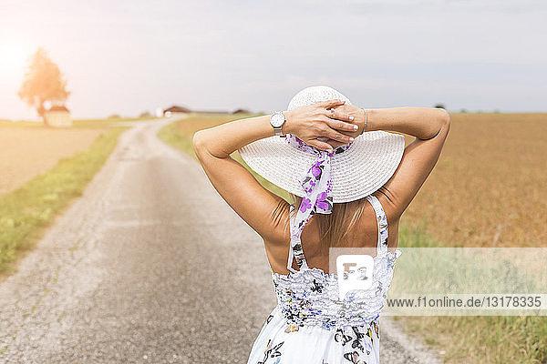 Rückansicht einer reifen Frau mit Hut auf einem abgelegenen Feldweg im Sommer