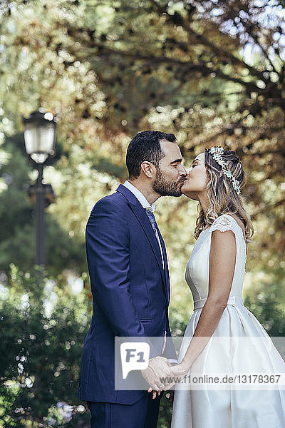 Happy bridal couple kissing in a park while holding hands