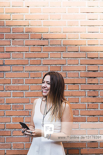 Laughing young woman in front of a brick wall using smartphone