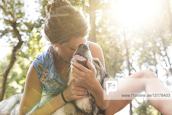 Young woman cuddling her dog in the woods