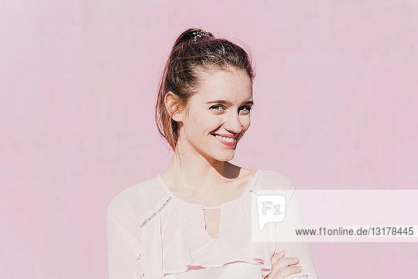 Porträt einer lächelnden jungen Frau vor rosa Wand