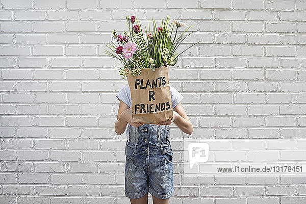 Girl hiding behind paper bag with flowers