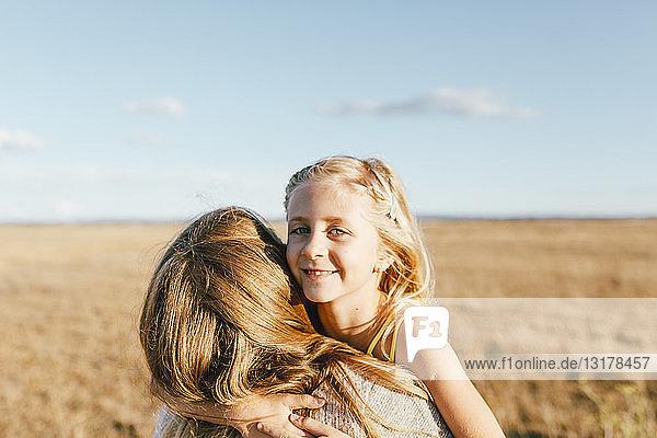 Porträt einer lächelnden Tochter  die ihre Mutter auf einem Feld umarmt