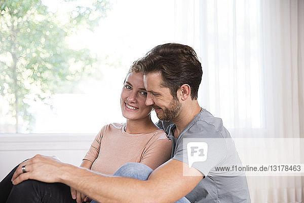 Lächelndes Paar entspannt zu Hause vor dem Fenster