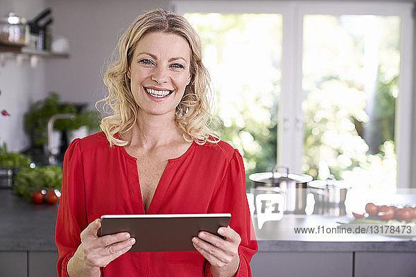 Porträt einer lächelnden Frau  die eine Tablette in der Küche hält