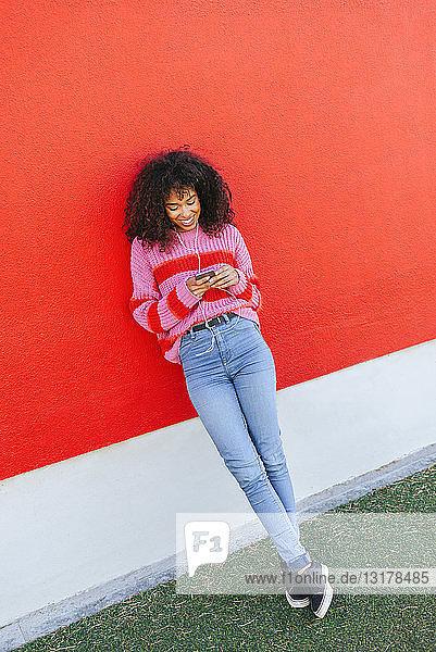 Lächelnde junge Frau mit Kopfhörern  die an einer roten Wand lehnt und auf ihr Handy schaut