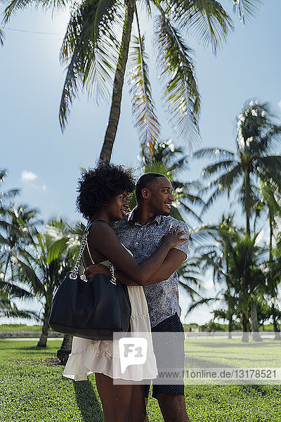 USA  Florida  Miami Beach  happy young couple embracing at palm trees in summer