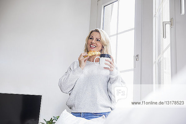 Portrait of smiling blond mature woman with croissant and coffee mug at home