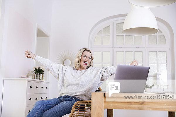 Porträt einer glücklichen blonden reifen Frau mit Laptop zu Hause