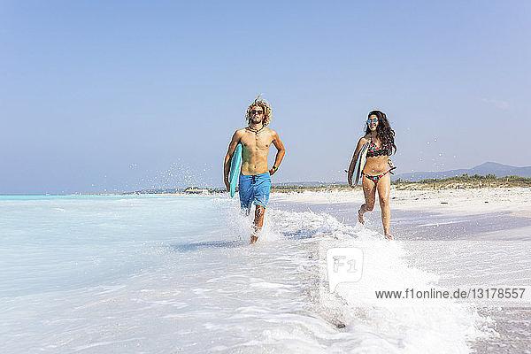 Paar  das am Strand läuft und Surfbretter trägt