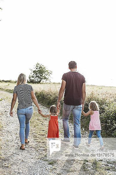 Rückansicht einer Familie mit zwei Töchtern  die Hand in Hand auf einem Feldweg gehen