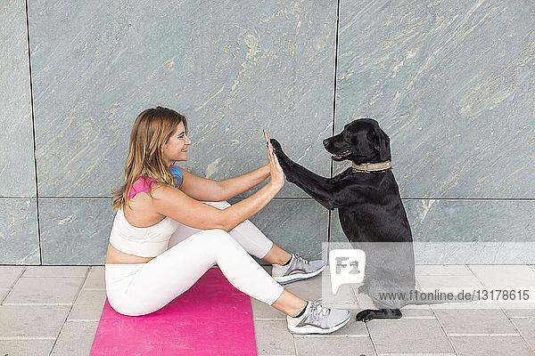 Junge Frau sitzt auf Yogamatte und macht Entspannungsübung mit ihrem schwarzen Hund