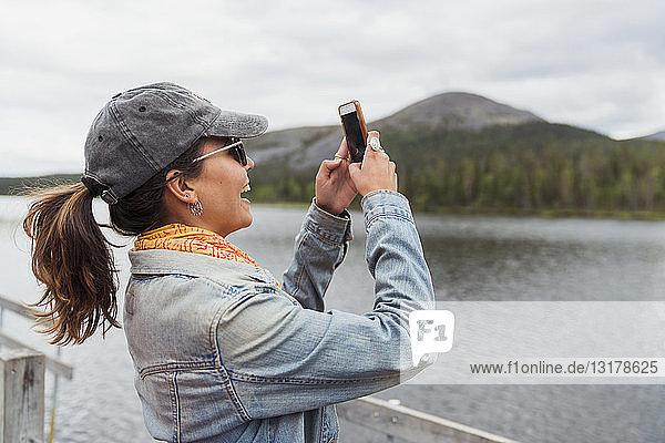 Finnland  Lappland  glückliche Frau auf einem Bootssteg an einem See bei einem Selfie
