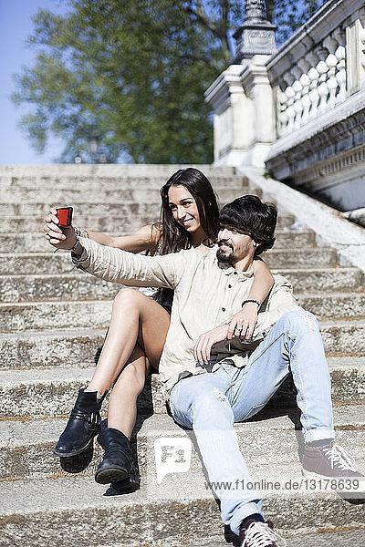 Glückliches junges Paar sitzt auf der Treppe und macht sich mit dem Smartphone selbstständig