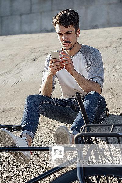 Junger Mann mit Pendler-Fixie-Fahrrad sitzt mit Handy an Betonwand