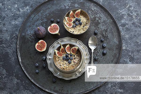 Schalen mit Brei mit in Scheiben geschnittenen Feigen  Blaubeeren und getrockneten Beeren