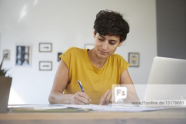Frau  die zu Hause am Tisch arbeitet