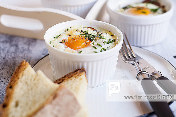 Oefs en cocotte (Individual baked eggs) with spinach  feta  bacon  eggs  and slices of bread