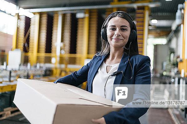 Junge Frau  die beim Paketdienst arbeitet und ein Paket im Lager trägt