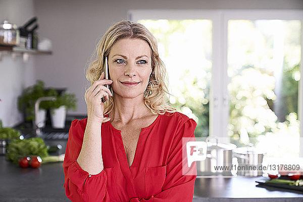 Porträt einer lächelnden Frau am Telefon in der Küche
