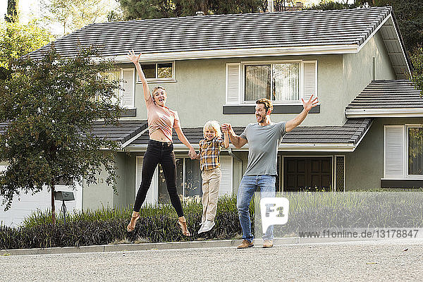 Happy family with son jumping in front of their home