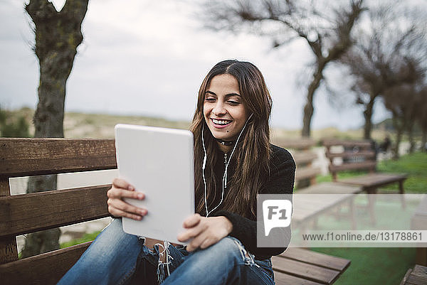Portrait of smiling young woman sitting on bench outdoors using tablet and earphones